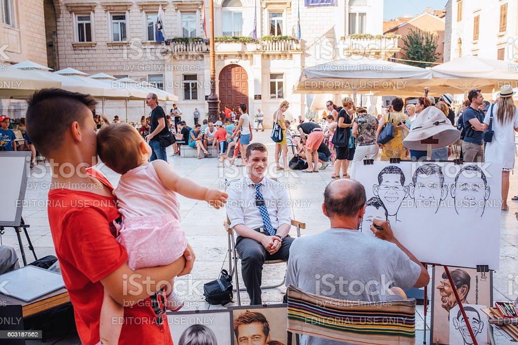 Street artist sketching portrait of tourists in Zadar, Croatia stock photo