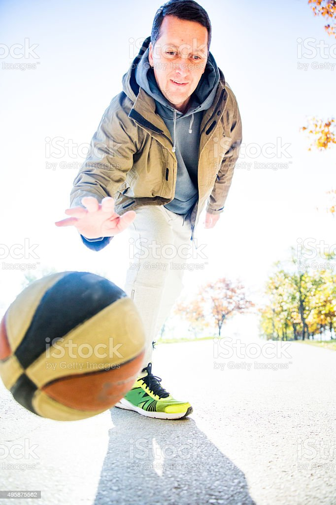 Man with basketball in autumn park