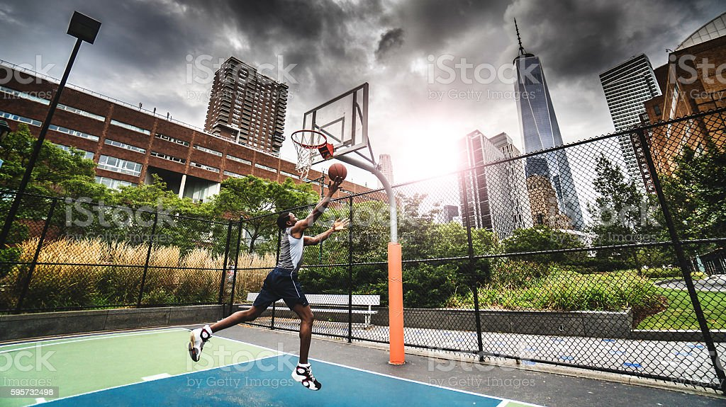 street basketball player doing a slam dunk stock photo