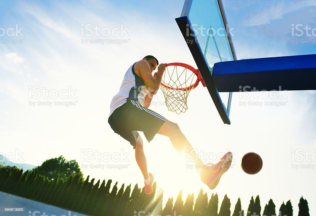 Street basketball player performing power slum dunk. stock photo