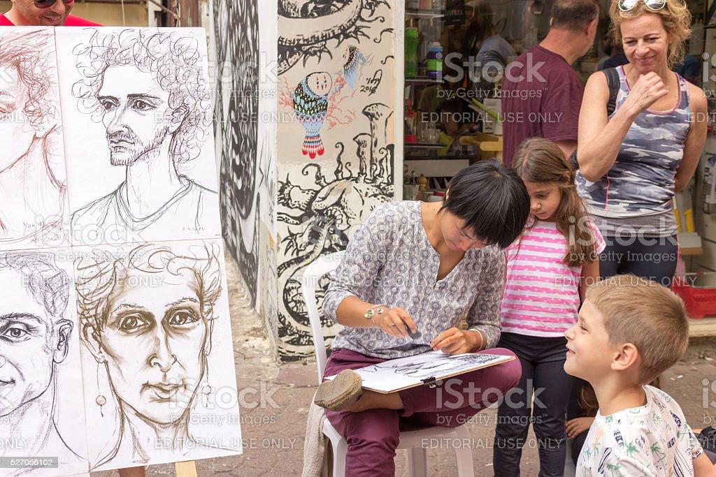 Street cartoonist draws a caricature stock photo