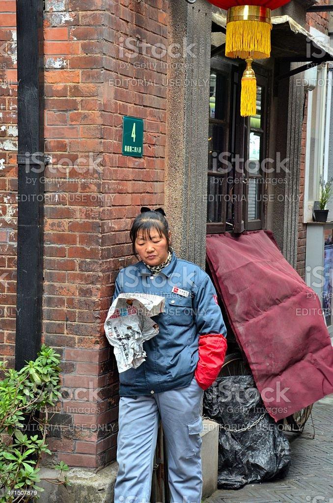 Street cleaner reads newspaper Shanghai China stock photo