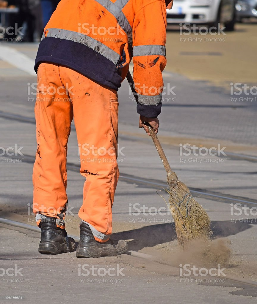 Street cleaner works with a broom stock photo
