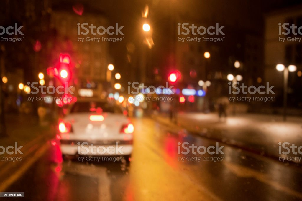 Out of focus rainy night street view , red traffic lights, street...