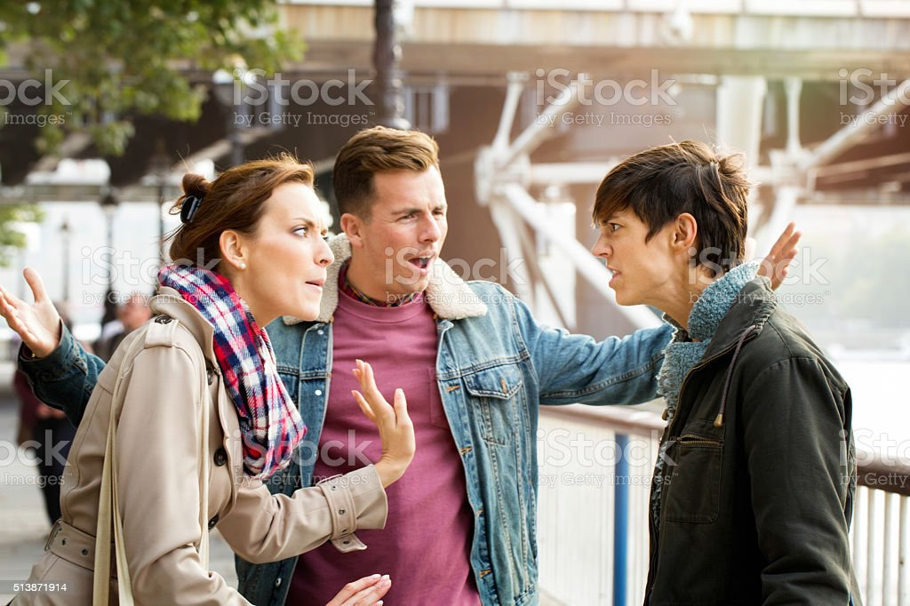 Street fight between three young British people stock photo