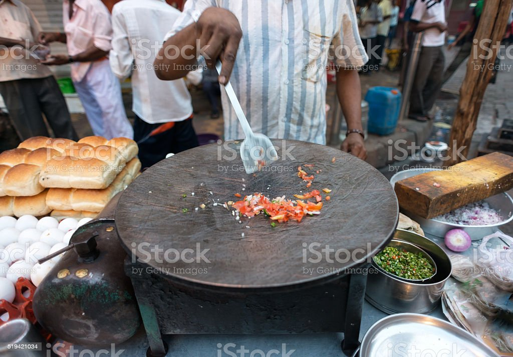 Street Food Vendor Cooking Peppers, Onions for Omelette, Mumbai, India stock photo