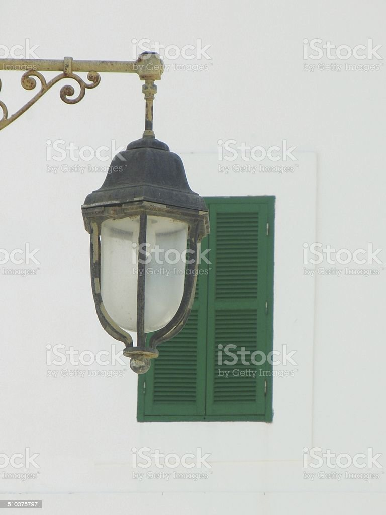 Street lamp before a green window shutter stock photo