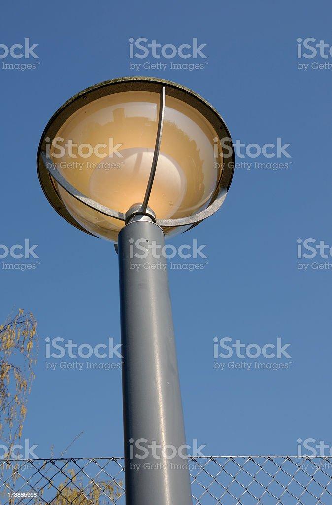 street light lit in daytime stock photo