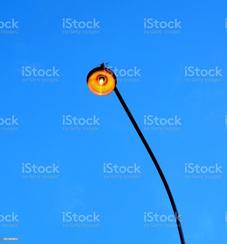 Street lighting lamp lit at dusk on a long pole stock photo