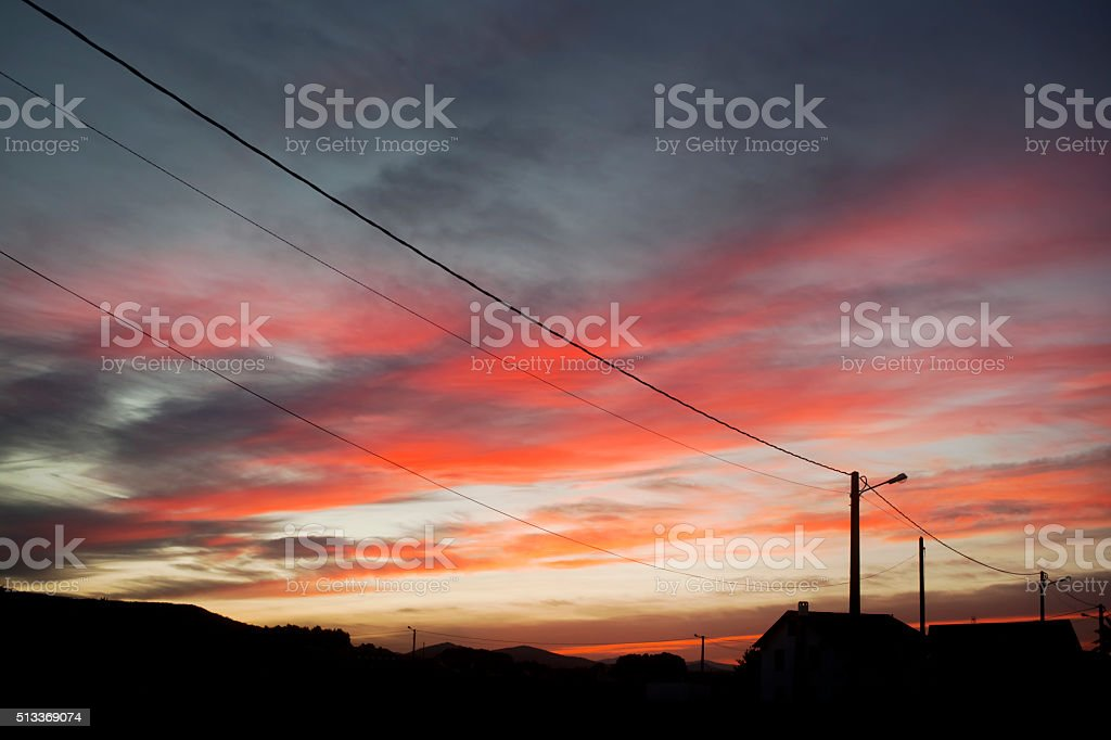 Perspective of road street lights, cables, roof silhouetted and...