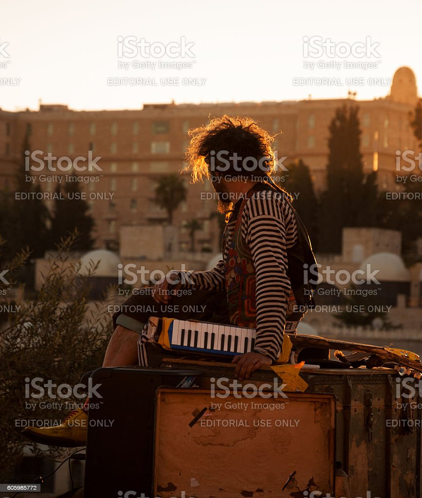 Street musician admiring Jerusalem landscape during sunset. stock photo
