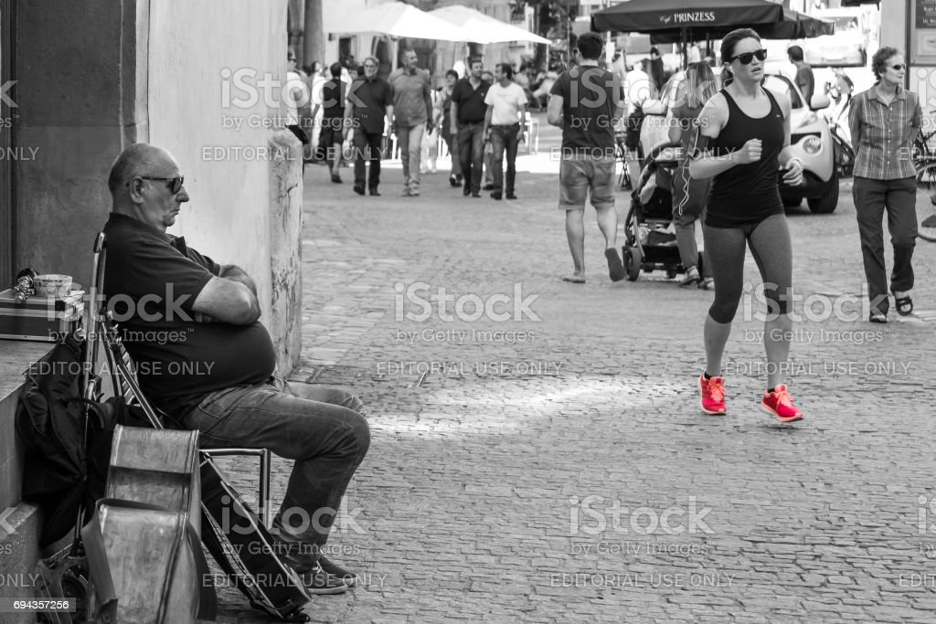 Street musician at the pedestrian zone in Regensburg and a jogging girl stock photo