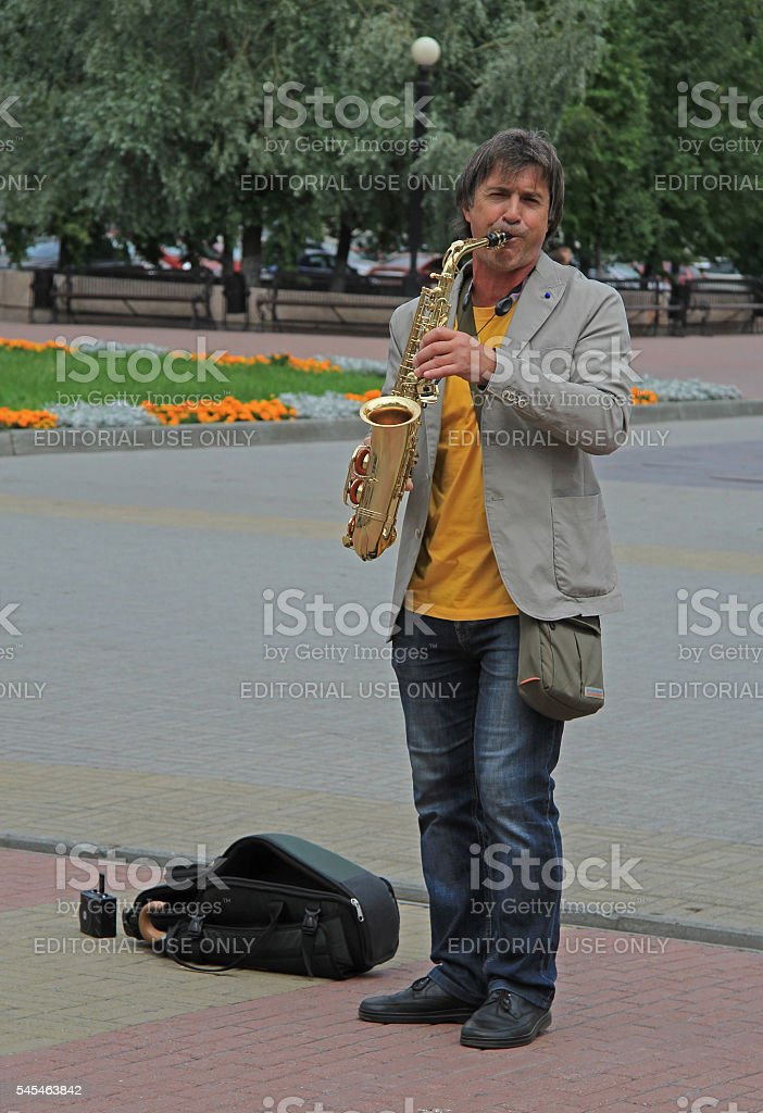 street musician is playing saxophone outdoor in Chelyabinsk, Russia stock photo
