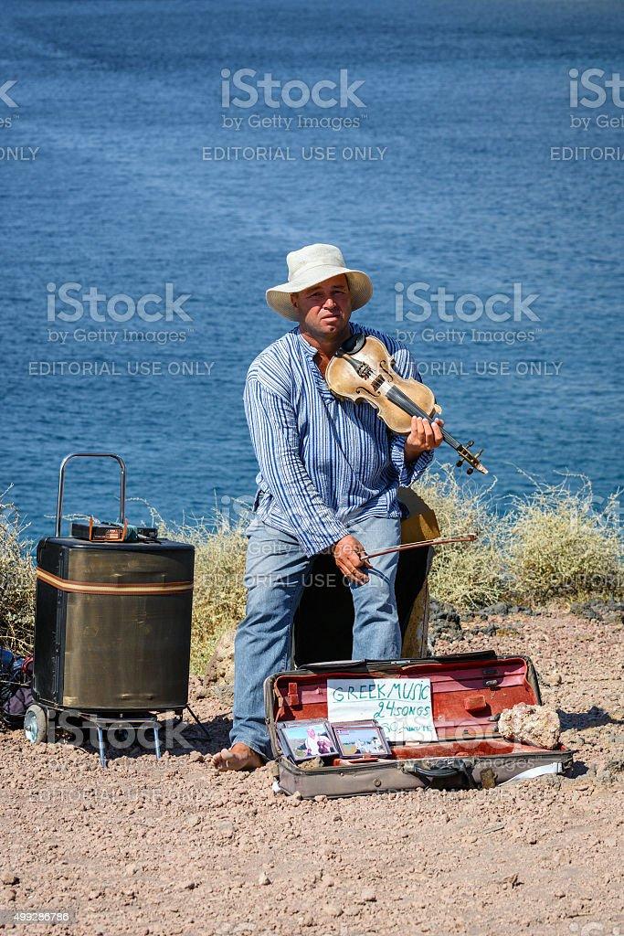 Street musician is playing violin near water on Santorini island stock photo