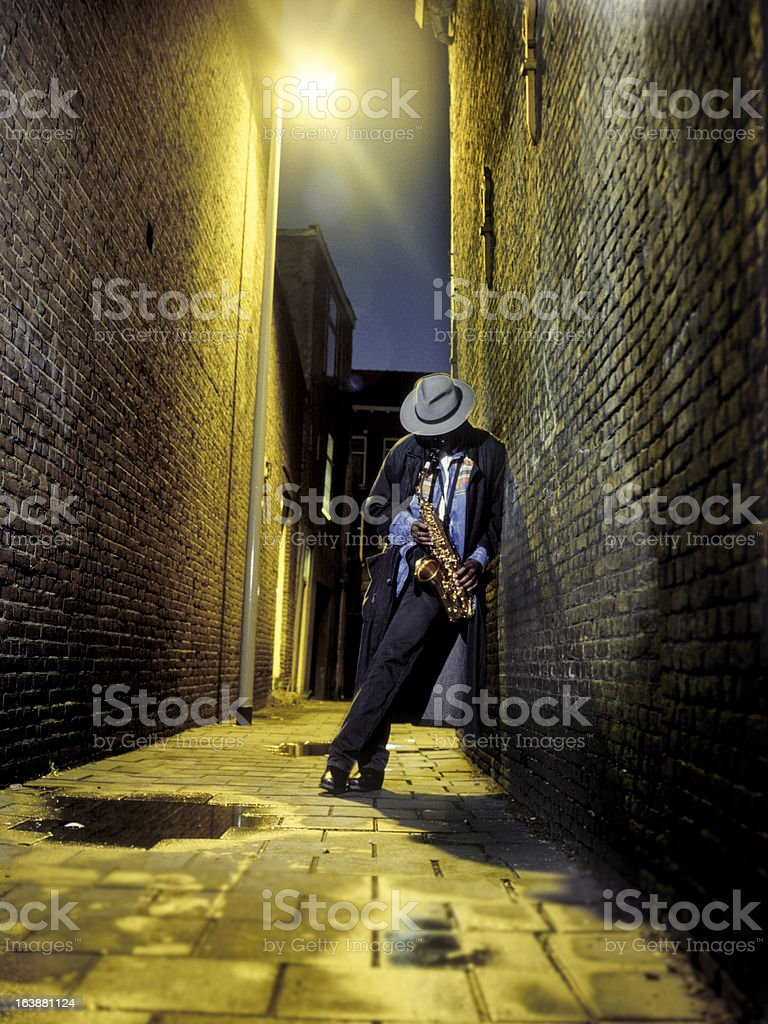 street musician playing saxophone in alley royalty-free stock photo