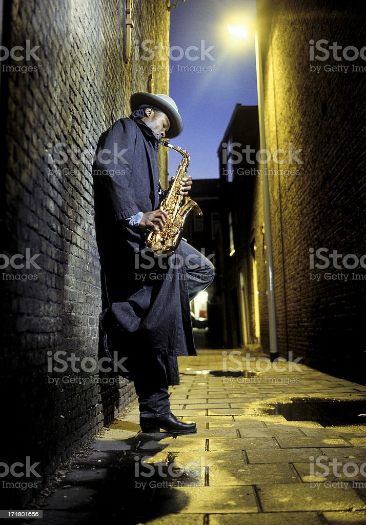 street musician playing saxophone in alley stock photo