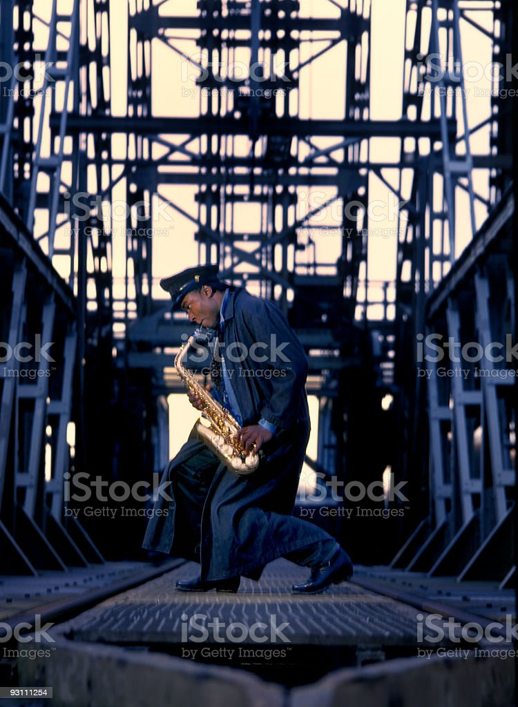 street musician playing the saxophone on railway bridge at dawn royalty-free stock photo