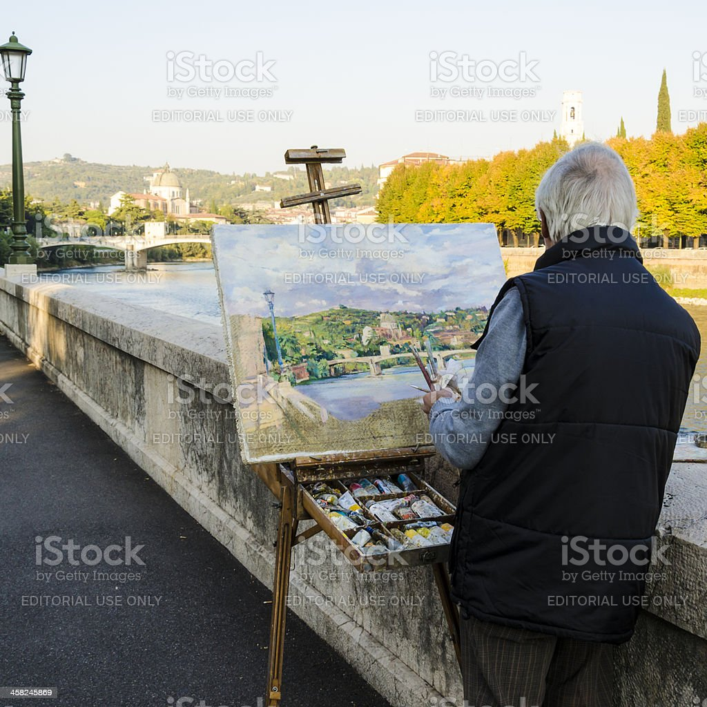 Street painter holding paintbrushes and painting Verona royalty-free stock photo