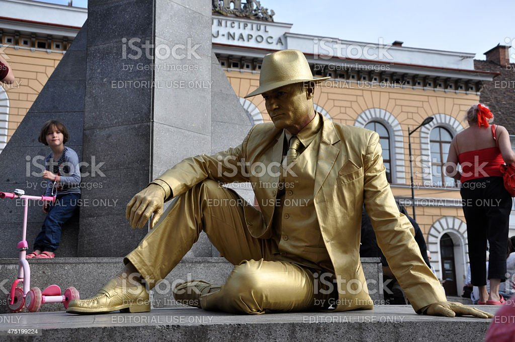Street performer, living statue in golden costume stock photo