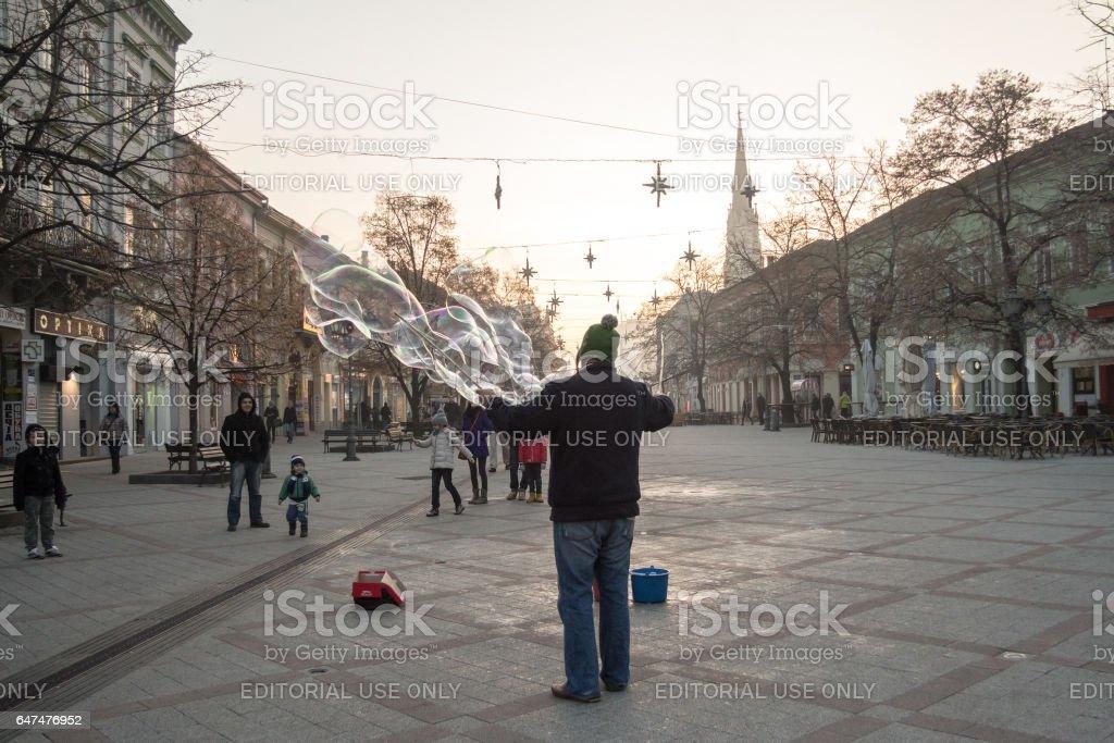 Novi Sad, Serbia - December 13, 2015: Street performer making soap bubbles in order to amuse people passing by pn Novi Sad main street, Zmaj Jovina stock photo