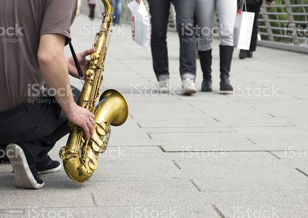 Street performer musician playing saxophone music to London pedestrians stock photo