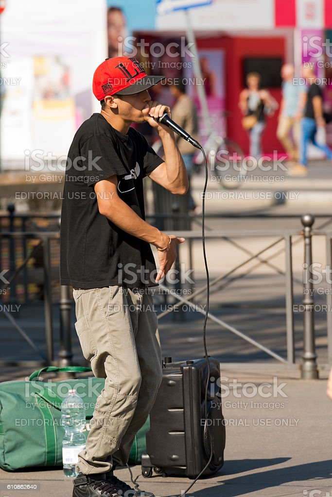 A boy beatbox performs in a street of the city center of Milan . The...