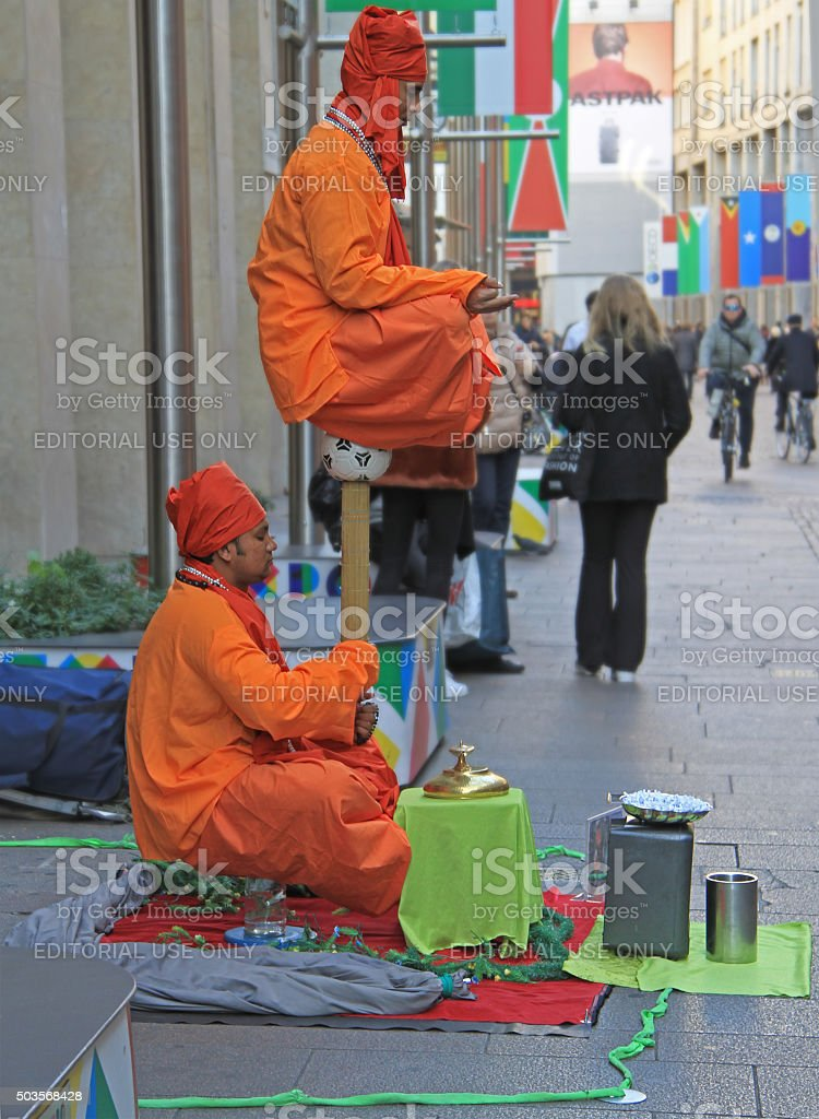 Street performers are showing a magical trick, levitation in the stock photo