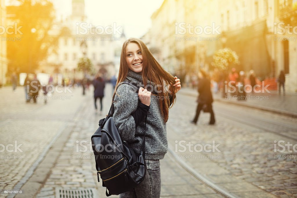 Street portrait of beautiful smiling young woman with backpack stock photo