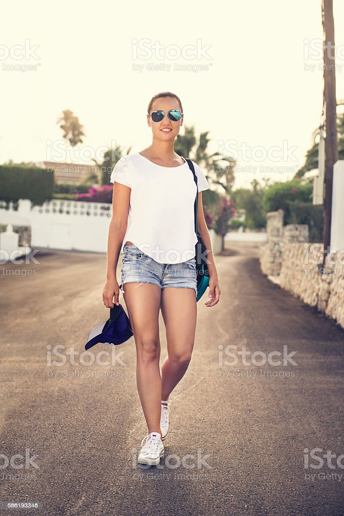 Street portrait of young, tanned woman walking down the street stock photo