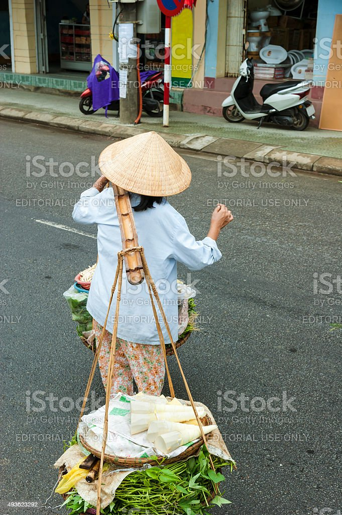 Street seller carries the pole balanced with two vegetable basket stock photo