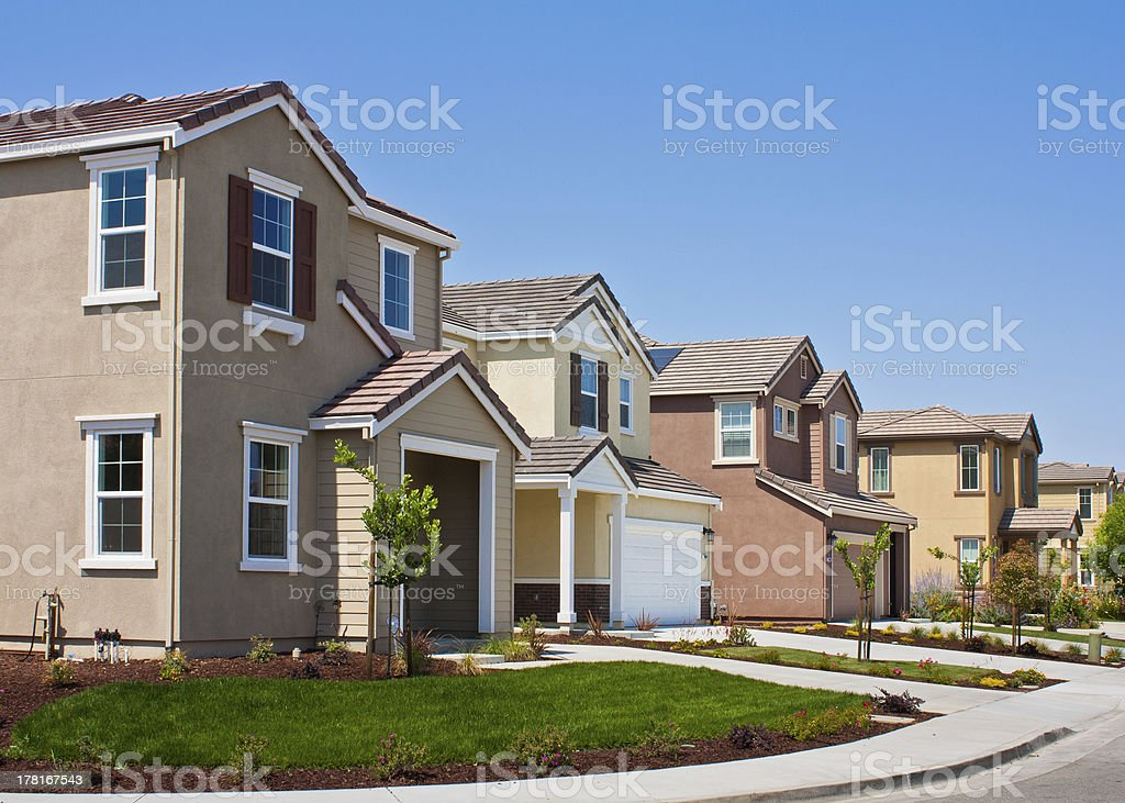 A street side view of four tract houses in a row stock photo