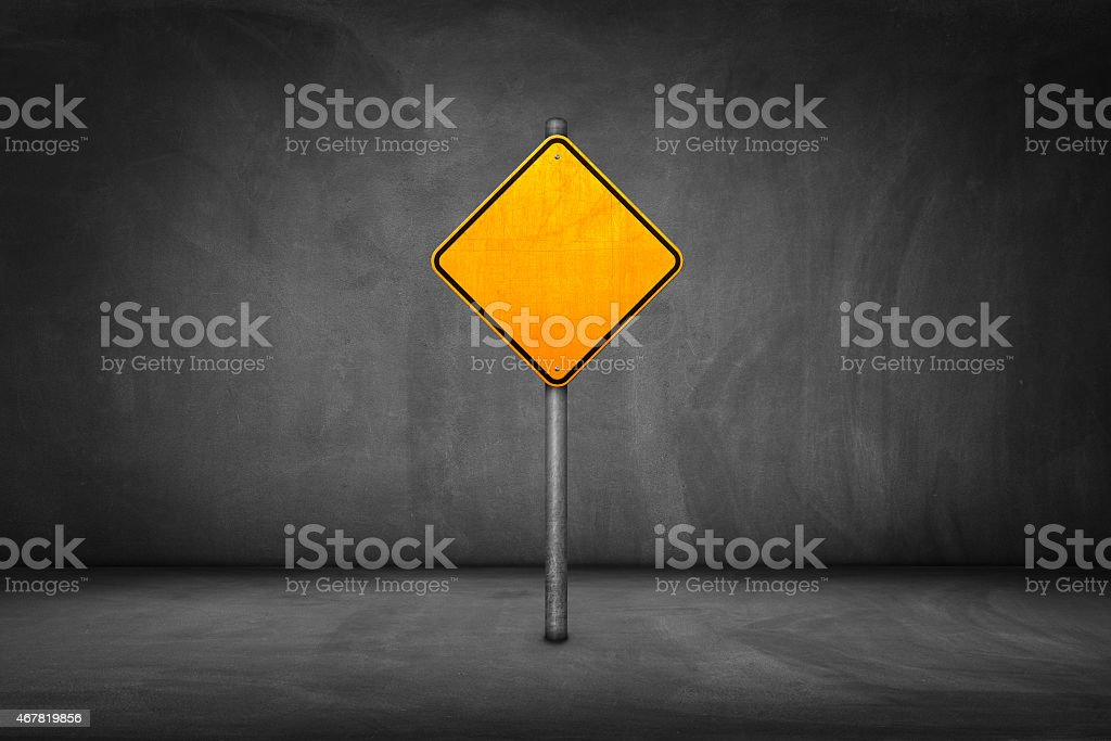 Street Sign: blank yellow road sign with street wall stock photo