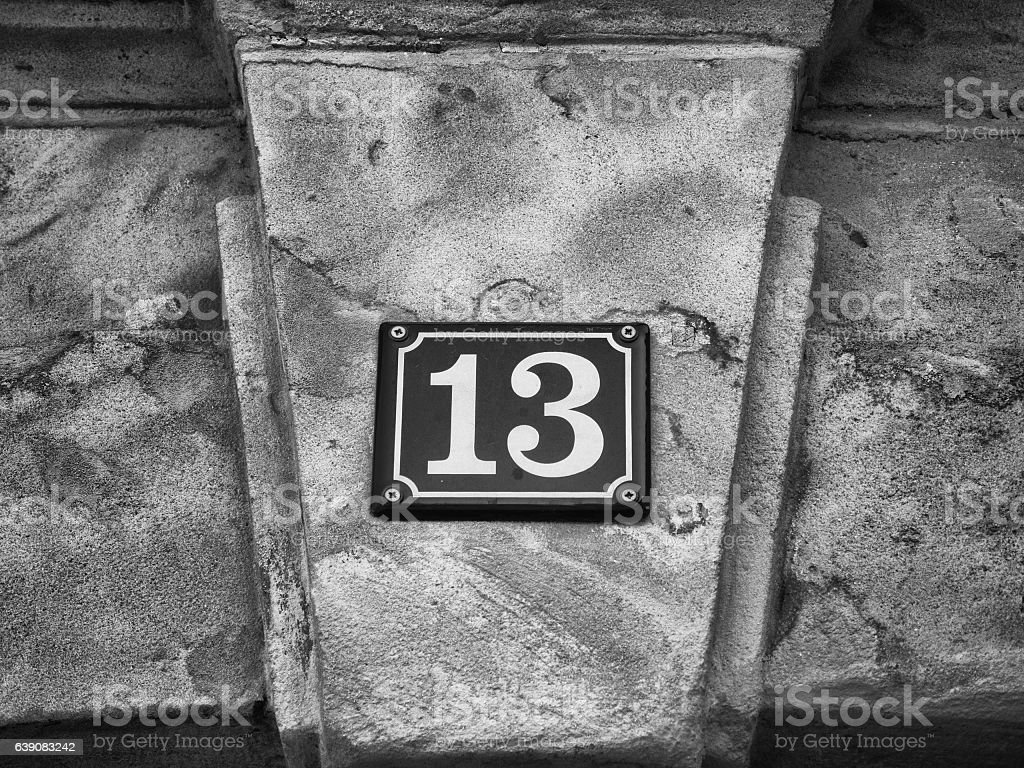 Street sign - House number 13 on sandstone wall stock photo