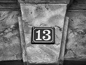 Street sign - House number 13 on sandstone wall
