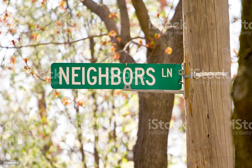 Street sign labelled 'Neighbors LN' with trees in background royalty-free stock photo
