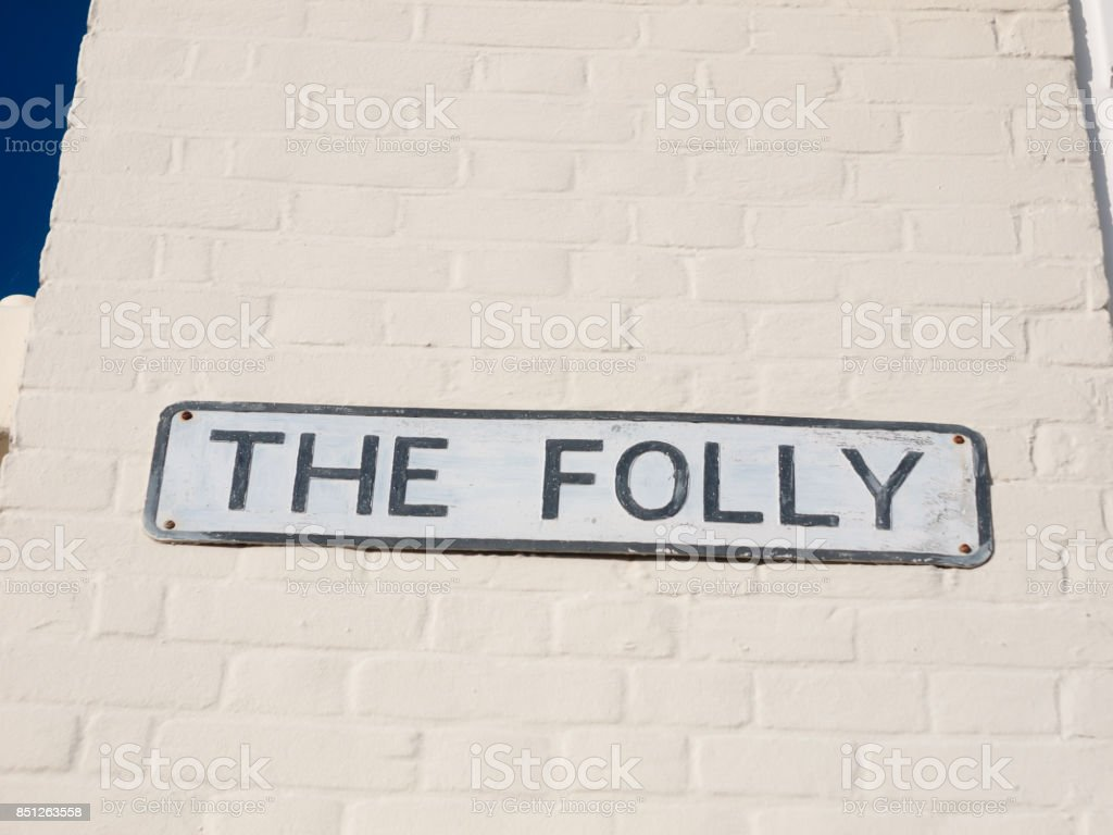 street sign name the folly white and black on wall stock photo