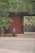 Street sweeper cleaning paved courtyard in Lama temple in Beijing