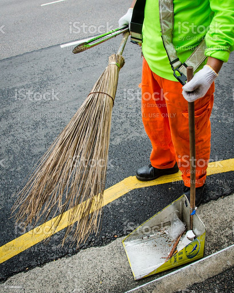 Street sweeper in Singapore uses traditional broom and makeshift pan stock photo