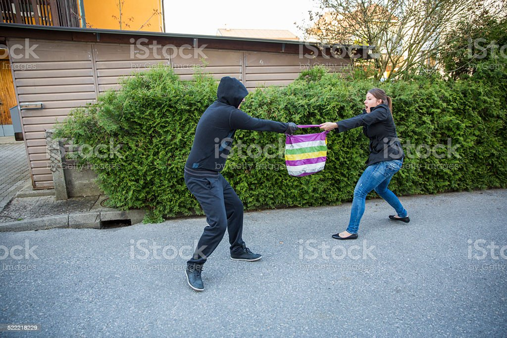 Street thief stealing womans bag...woman is fighting for her property stock photo