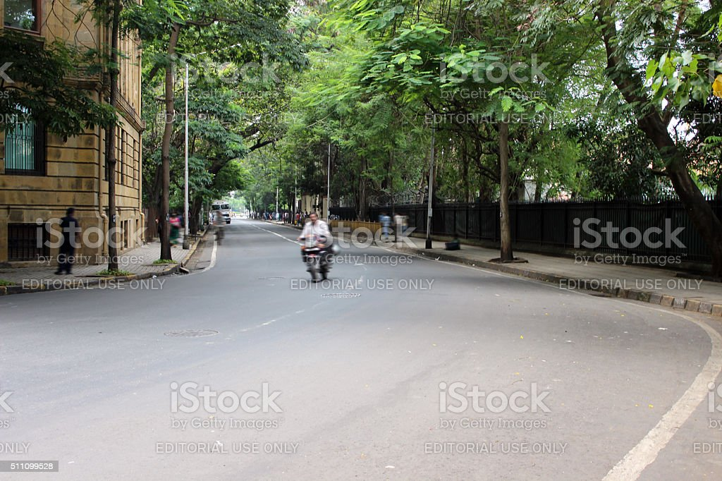 street turn in city surrounded by trees stock photo