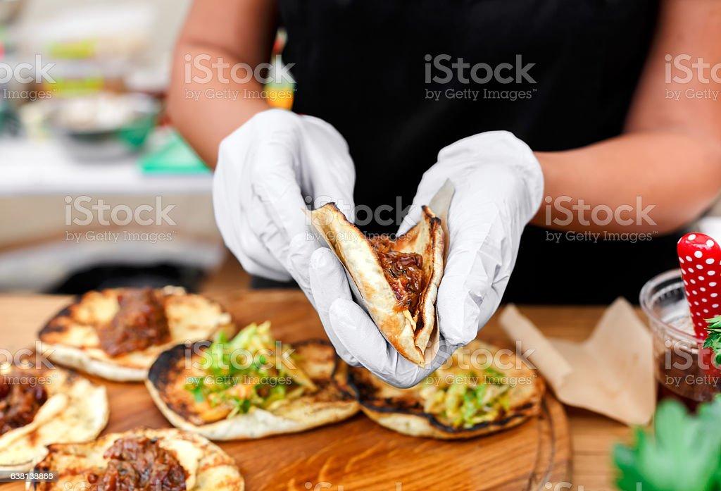Street vendor hands making taco outdoors stock photo