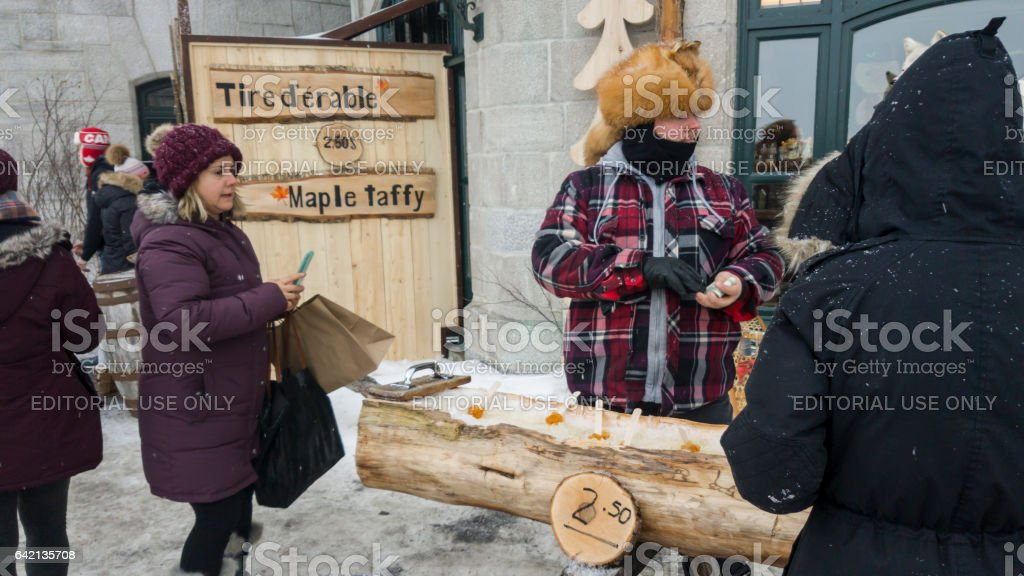 Street vendor selling maple toffee made of hot maple syrup in Quebec, Canada. stock photo
