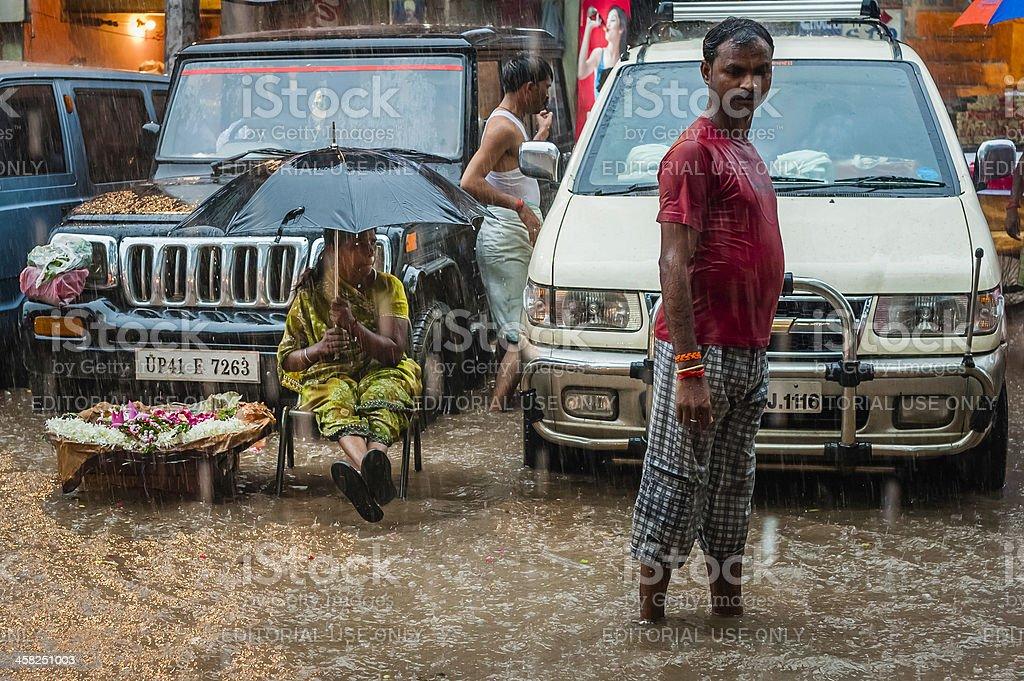 Street vendor sells flowers during flash flood, Varanasi, India. royalty-free stock photo