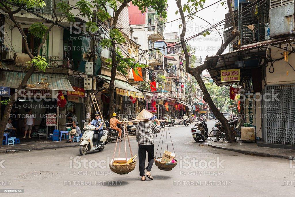 Street vendor transporting goods in baskets in Hanoi stock photo