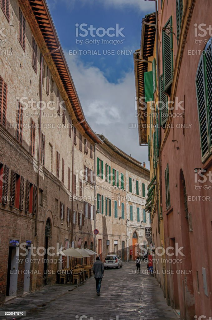 Street view and tall buildings in a cloudy day at the town of Siena stock photo