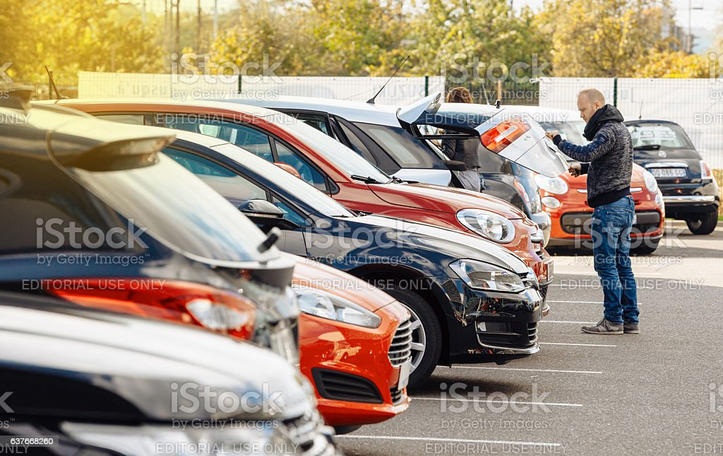 Street view of man choosing new car stock photo