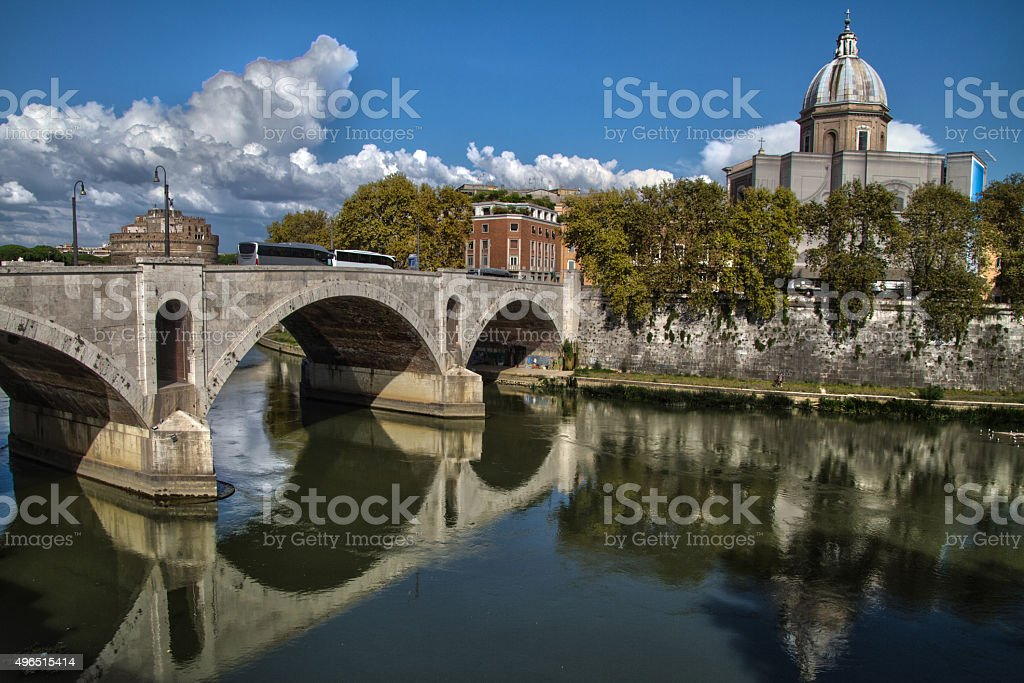 street view of reflections of bridge and church in Tiber river stock photo