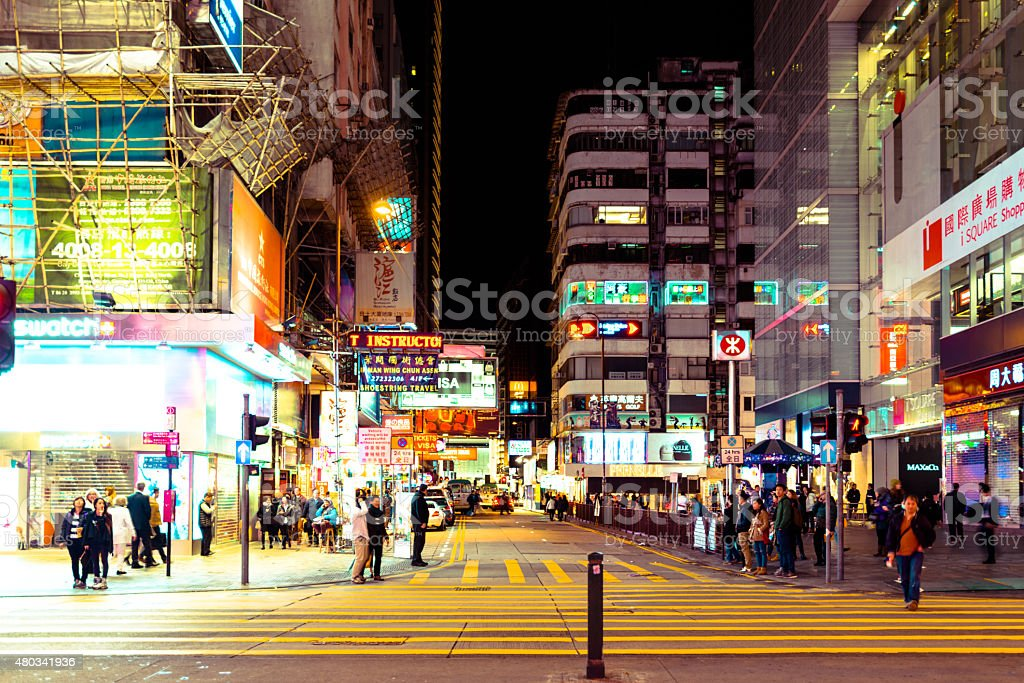 Street view with traffic and shops at night stock photo