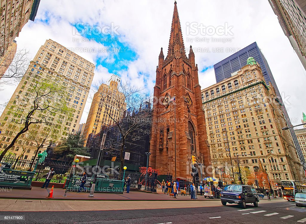 Street with tourists and traffic and Trinity Church in Manhattan stock photo