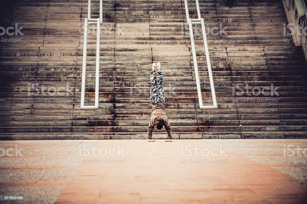 Young man doing handstand on bottom of the stairs.